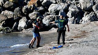 Des membres de la garde civile espagnole prenant en charge un migrant arrivant par la mer dans l'enclave de Ceuta, le 17 mai 2021