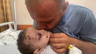 يحتضن محمد الحديدي طفله الرضيع عمر داخل مستشفى في غزة الناجي الوحيد من الغارات الجوية الإسرائيلية.