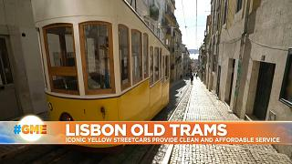 Iconic yellow streetcar up a hill in Lisbon, Portugal