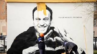A painting of Russia's imprisoned opposition leader Alexei Navalny is painted over by municipal workers in St. Petersburg