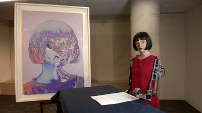 Ai-Da, the artificially intelligent robot, poses next to her self-portrait currently on display in the London Design Museum.