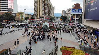 """يقف الناس بالقرب من """"سيغ بلازا"""" التي يبلغ ارتفاعه 300 متر بعد أن بدأ في الاهتزاز، في  شينجن بمقاطعة قوانغدونغ جنوب الصين -  18 آذار / مايو 2021"""