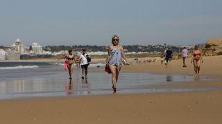 Turistas pasean por la playa en el Algarve