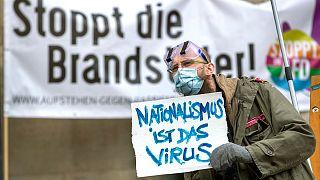 Ativista numa contramanifestação a criticar um protesto negacionista na Alemanha