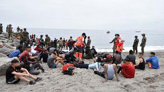 يساعد أعضاء الصليب الأحمر المهاجرين الذين وصلوا سباحة إلى جيب سبتة الإسباني بحضور الجنود الإسبان وأفراد الحرس المدني الإسبان في 18 مايو / أيار 2021 في سبتة.
