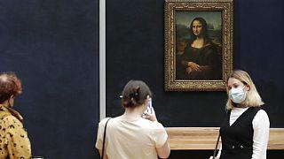 Visitante posa com máscara em frente à Mona Lisa, no Museu do Louvre
