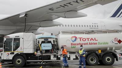 Workers refuel an Airbus A350 with sustainable aviation fuel at Roissy airport, north of Paris, Tuesday, May 18, 2021.