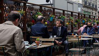 Emmanuel Macron et Jean Castex en terrasse d'un établissement parisien, prenant un café devant de nombreux objectifs, le 19 mai 2021