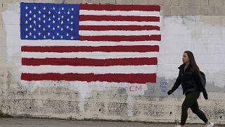 فتاة أمريكية تسير بجانب حائط رُسم عليه علم الولايات المتحدة في أحد شوارع سان فرانسيسكو