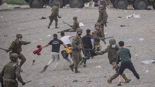 Un grupo de soldados se enfrenta a migrantes en la playa de Ceuta