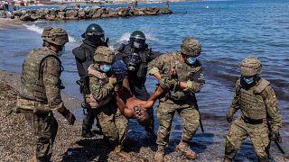 جنود الجيش الإسباني يطردون مهاجرا من جيب سبتة الإسباني، الثلاثاء 18 مايو 2021.