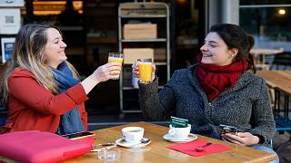 Women enjoy a cafe and an orange juice at a café terrace Wednesday, May, 19, 2021 in Strasbourg, eastern France.