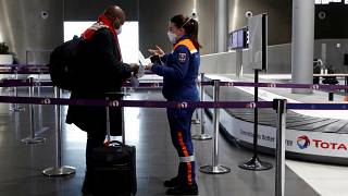 A member of Civil Protection checks air travellers documents at Paris Charles de Gaulle airport