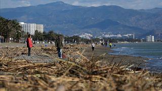People walk along the beach after storm Gloria battered Spain's eastern coast in Torremolinos, Spain, Sunday, Jan. 26, 2020