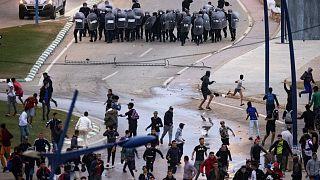 مهاجرون في مواجهة مع شرطة مكافحة الشغب المغربية في بلدة الفنيدق الشمالية الواقعة بالقرب من الحدود بين المغرب وجيب سبتة في شمال إفريقيا في 19 مايو 2021.