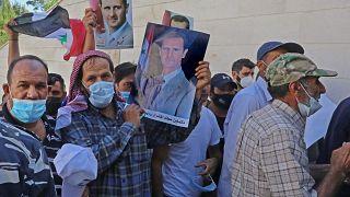 ناخبون سوريون مقيمون في لبنان يحملون صوراً للرئيس بشار الأسد،  أمام السفارة السورية بعبدا لبنان.