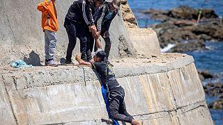 مهاجرون قاصرون يتسلقون جدارًا بحريًا في مدينة الفنيدق الشمالية بعد محاولتهم عبور الحدود من المغرب إلى جيب سبتة الإسباني في شمال إفريقيا في 19 مايو 2021.