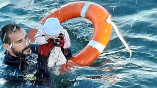 a member of the civil guard rescues a baby that was separated from its migrants parents, Spain