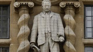 A statue of Cecil Rhodes, a controversial Victorian imperialist, stands mounted on the facade of Oriel College in Oxford, England, June 17, 2020.