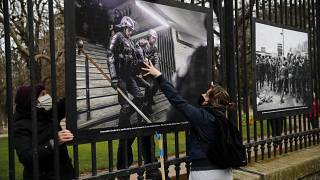 Photos of police violence are hung on the fences of the Luxembourg garden during a protest against the global security bill in Paris, Thursday, March 18, 2021.