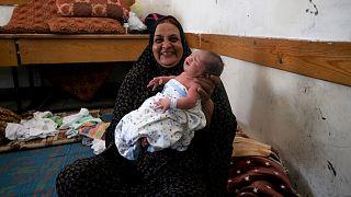امرأة فلسطينية تحمل رضيعا يبلغ من العمر يوما واحدا في إحدى مدارس الأمم المتحدة حيث تلجأ عائلات فلسطينية فقد منازلها بالقصف- غزة