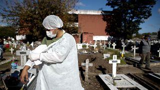 Un employé d'un cimetière argentin enlève sa blouse de protection après avoir déplacé un cercueil contenant une victime du Covid-19, à Buenos Aires, le 8 mai 2021.