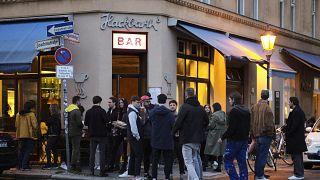 Un grupo de jovenes reunidops en la puerta de un bar en Berlín