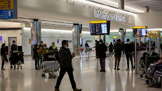 People wait and arrive in the arrivals area at Heathrow Airport in London, Tuesday, Jan. 26, 2021.