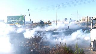 Tear gas canisters fired by Israeli forces landing on Palestinians during a protest near the DCO checkpoint, north of Ramallah