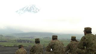 Members of self-defence forces watching exercises with Mount Fuji in the background
