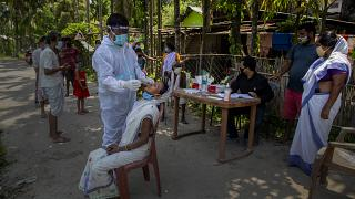An Indian health worker in protective suit takes the swab of a village woman to test for COVID-19 in Burha Mayong village, Morigaon district of Assam, India, May 22,