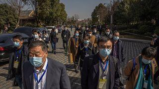 Kínai hivatalnokok távoznak egy tanácskozásról Vuhanban, 2021. január 29-én