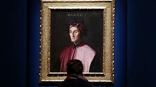 A woman looks at a portrait of poet Dante Alighieri at an exhibition, in Forlì, Italy, Saturday, May 8, 2021