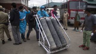 Local men hired by administration assist transport of oxygen cylinders in the premises of a hospital in Srinagar, Indian controlled Kashmir, Sunday, May 23, 2021.