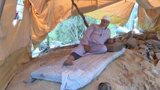 Nazmi Al-Dahdouh sitting in his tent set up over the rubble of his destroyed house