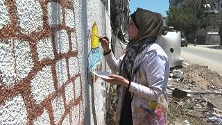فنانة فلسطينية ترسم على جدران مهدمة في غزة بعد القصف الإسرائيلي على القطاع المحاصر