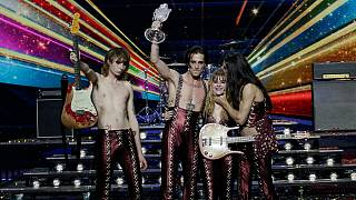 Members of the Maneskin from Italy Thomas Raggi, from left, Damiano David, Victoria De Angelis and Ethan Torchio pose on stage with the trophy after winning the Grand Final of