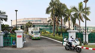 Yangon International Airport can be seen on Friday, Jan. 22, 2021, in Yangon, Myanmar, as traffic police lead trucks carrying COVID-19 vaccines.