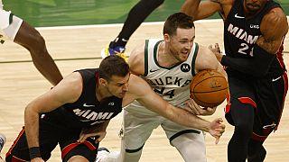 El escolta de los Milwaukee Bucks Pat Connaughton, en el centro, lucha por el balón contra los aleros de los Miami Heat