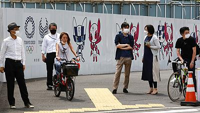 People stand by posters to promote the Tokyo Olympic Games scheduled to start in the summer of 2021, in Tokyo, Monday, May 24, 2021.