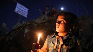 طفل فلسطيني يحمل شمعة خلال مسيرة وسط أنقاض المنازل التي دمرتها الغارات الإسرائيلية في مدينة غزة في 24 مايو 2021.