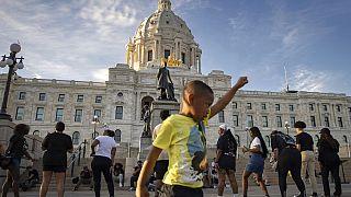 Un niño sostiene su puño en alto en una concentración organizada por el primer aniversario del asesinato de George Floyd el lunes 24 de mayo de 2021