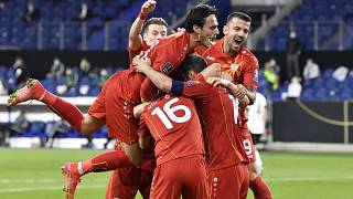 North Macedonia's players celebrate their first goal during a 2022 FIFA World Cup qualifying match against Germany.