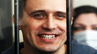 Belarus opposition figure Pavel Severinets smiles from the defendant's cage at a courthouse, on May 25, 2021