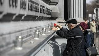 Elderly people light candles at the Wall of Heroes outside the House of Terror Museum to pay their tribute on the occassion of the Memorial Day of Victims of Communism.