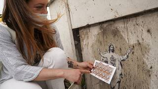 Artist Alessia Babrow holds the Vatican stamps next to her street art at the Vatican, May 14, 2021.