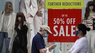 Shoppers pass a sale sign in a shop window on Oxford Street in London, Aug. 13, 2020.