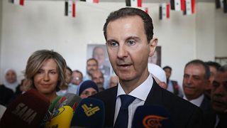 الرئيس السوري بشار الأسد وزوجته أسماء يدليان بصوتيهما في مركز اقتراع في دوما بالقرب من دمشق في 26 مايو 2021.