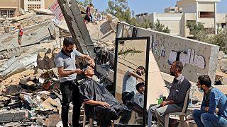 هاشم الجروشة، حلاق فلسطيني يعمل وسط أنقاض مبان ومتاجر دمرتها الغارات الإسرائيلية  في مدينة غزة. 25 مايو 2021.
