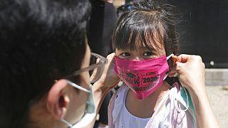 Vater hilft seiner Tochter beim richtigen Aufsetzen eines Nasen-Mund-Schutzes, 10.06.2020